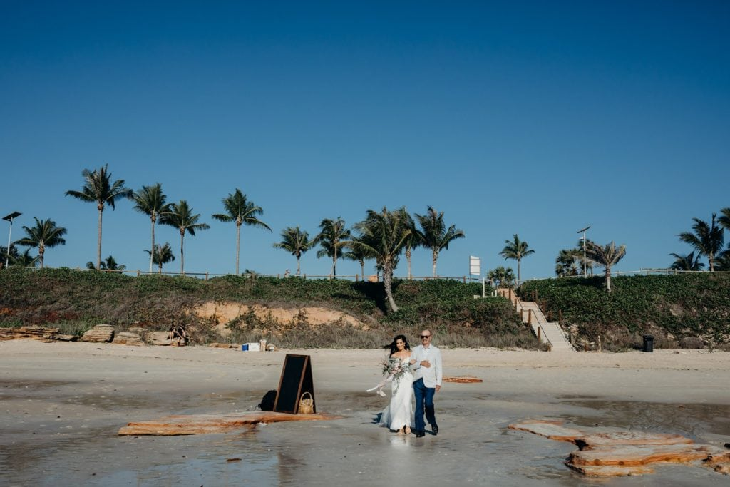 father walks his daughter along Cable Beach to her beach wedding ceremony