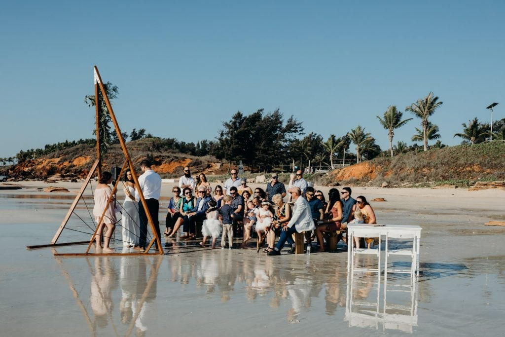 small wedding on the beach with red pindan cliffs in the background