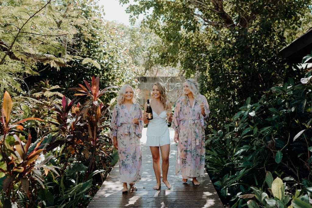 three women in robes walking along wooden path at Broome Resort with Champagne
