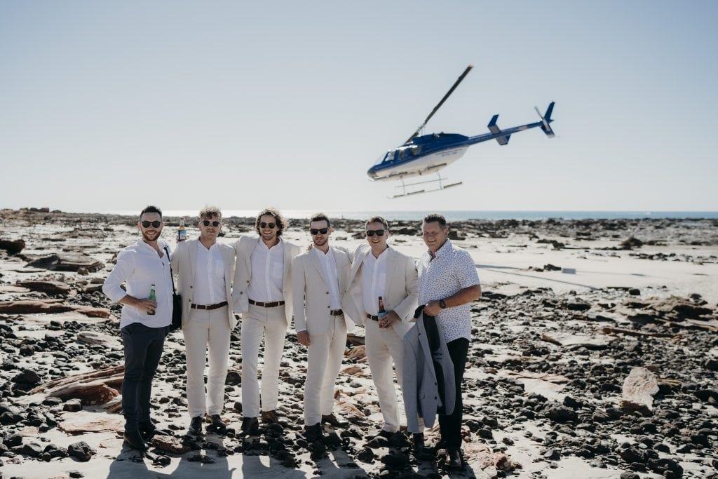 Groom and his groomsmen standing in front of helicopter to Wedding at Gantheaume Point