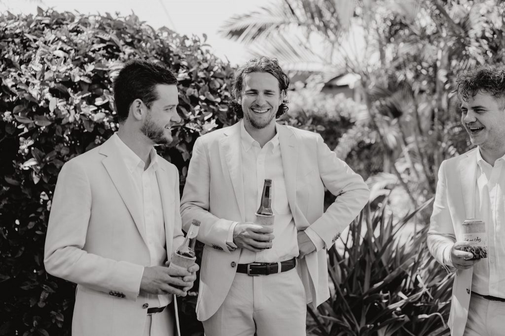 three brothers standing in tropical garden with beers in their hands and laughing