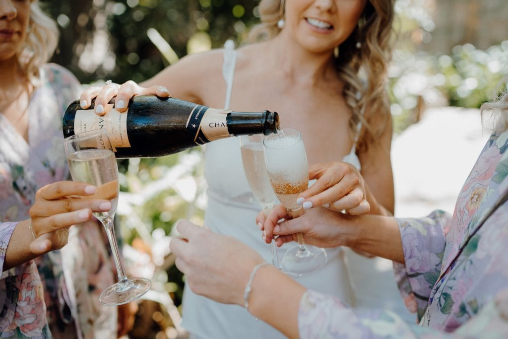 close up of hands pouring glasses of Champagne at Billi Resort in Broome