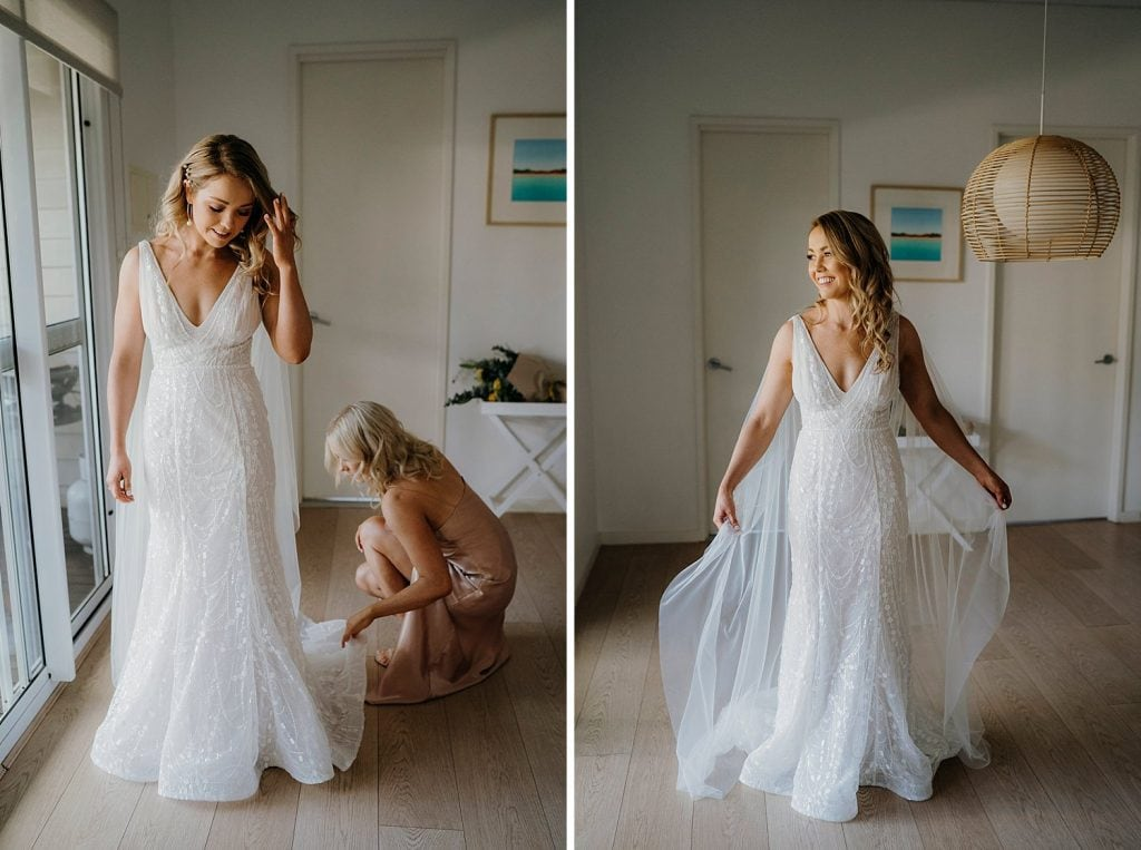 bride is getting into her wedding dress with the help of her sister