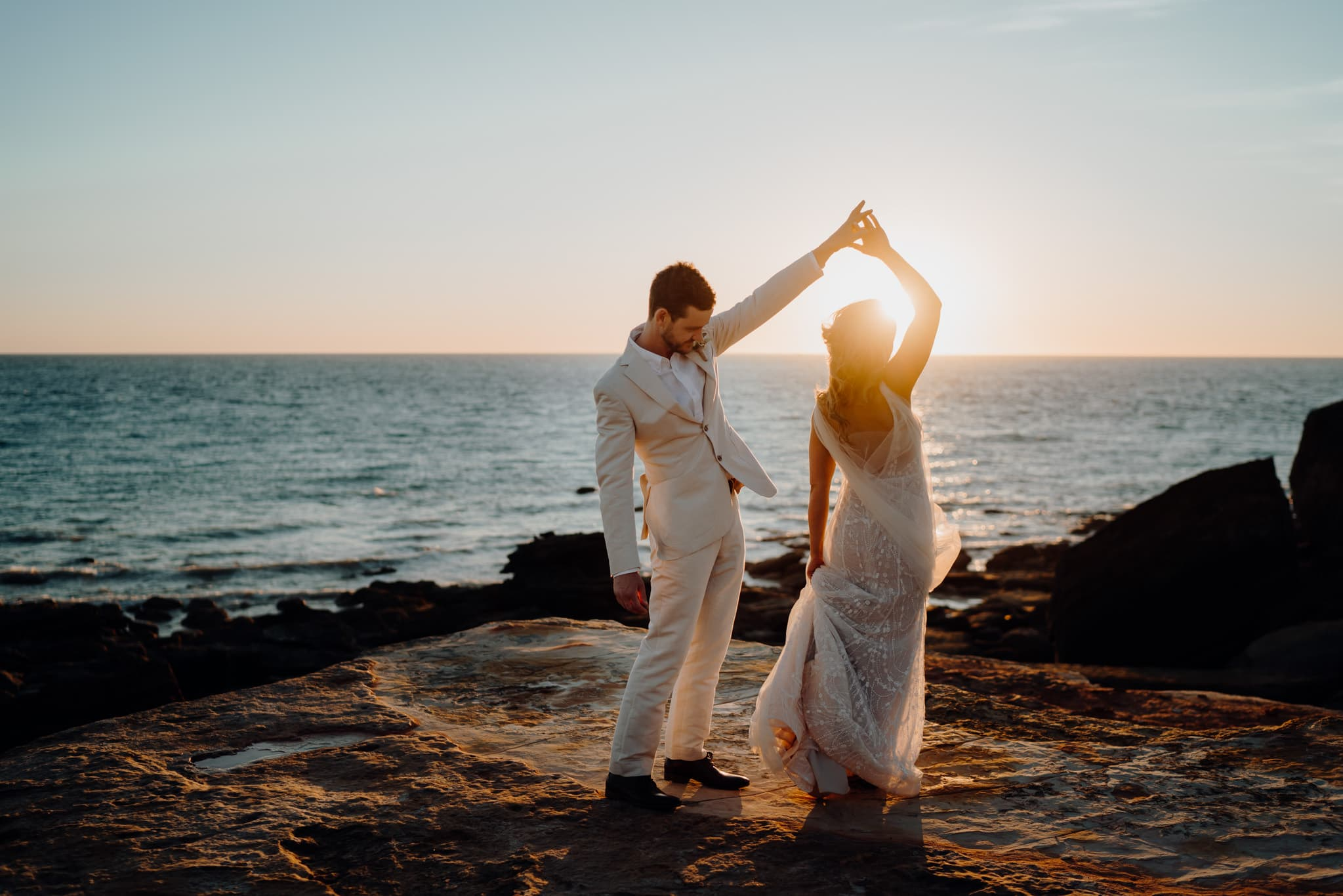 bride and groom dancing on clifftop at Gantheaume Point in Broome at sunset