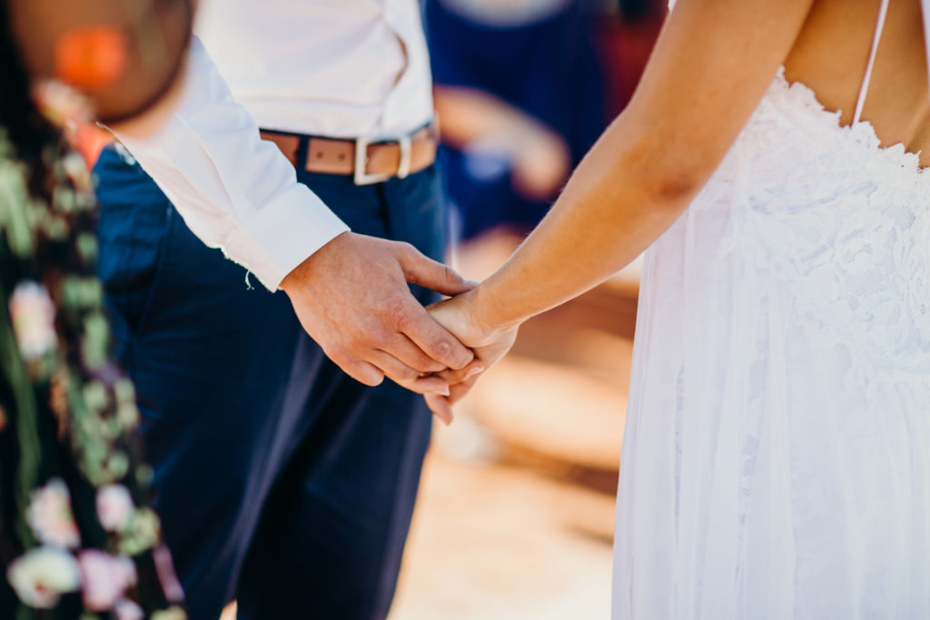 close up of bride and groom holding hands during ther at Broome Fishing Club wedding ceremony