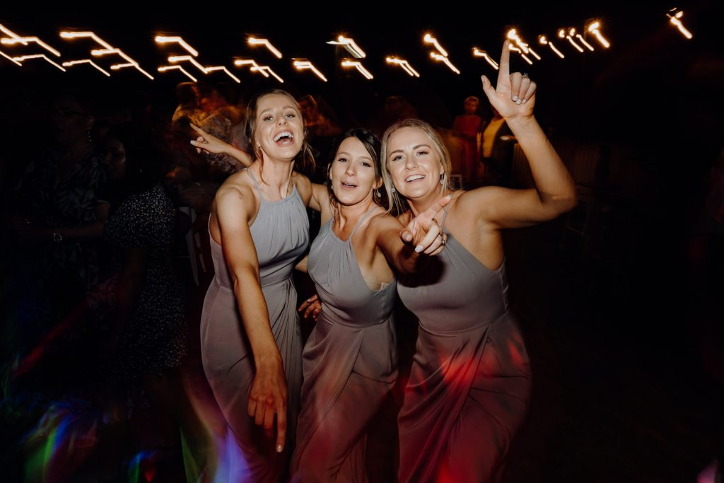 three bridesmaids in grey dresses on the dancefloor at Broome surf club