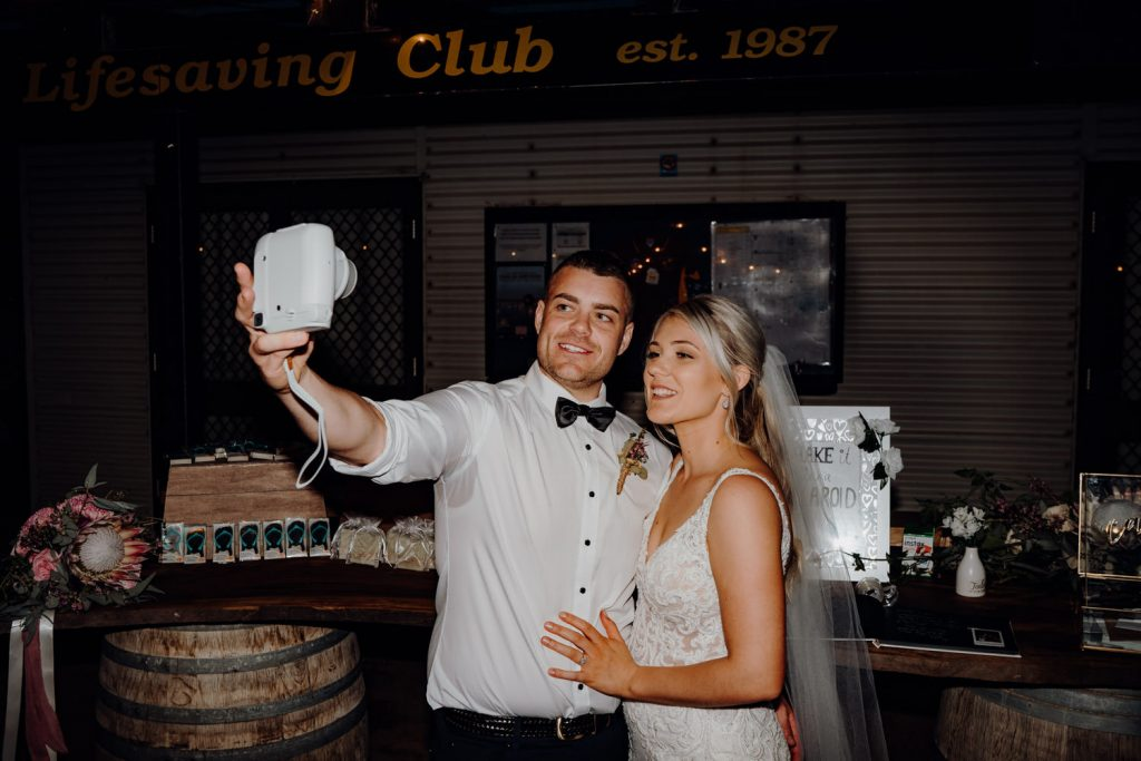 wedding couple taking a selfie with a polaroid camera at their relaxed beach wedding
