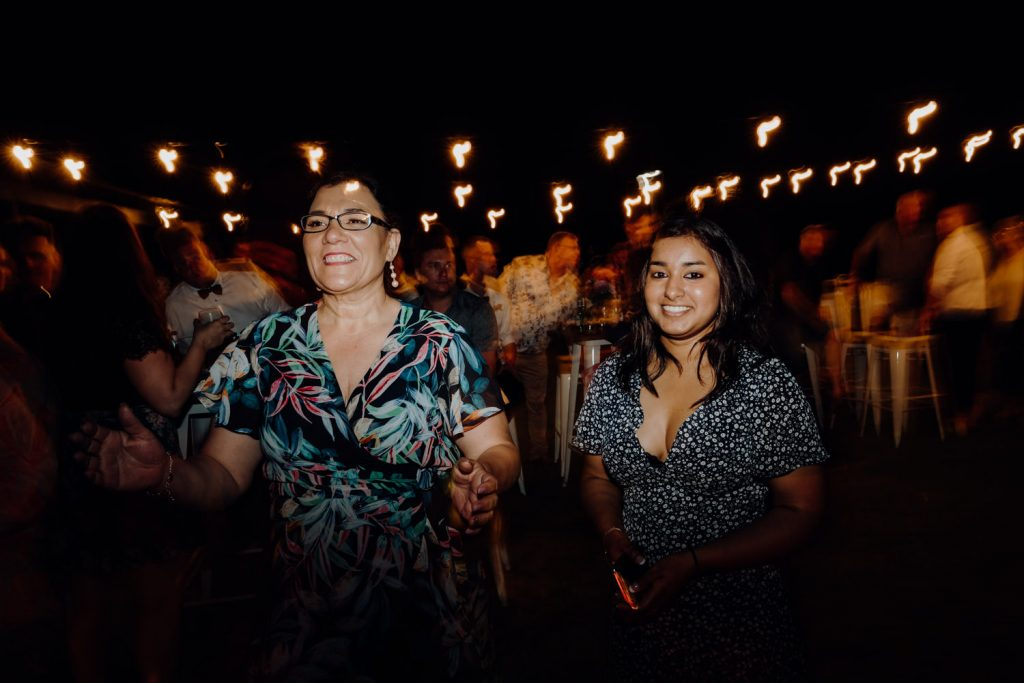 relaxed beach wedding reception with two women dancing under festoon lights