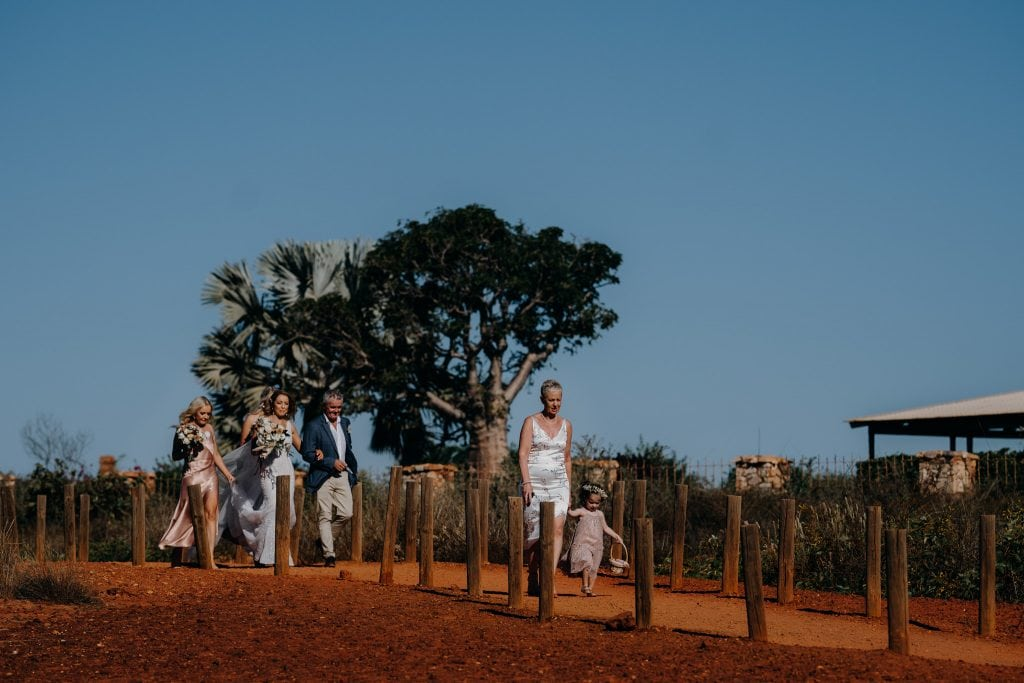 bride in white dress is walking along the path with her parents and sisters towards her wedding at Gantheaume Point