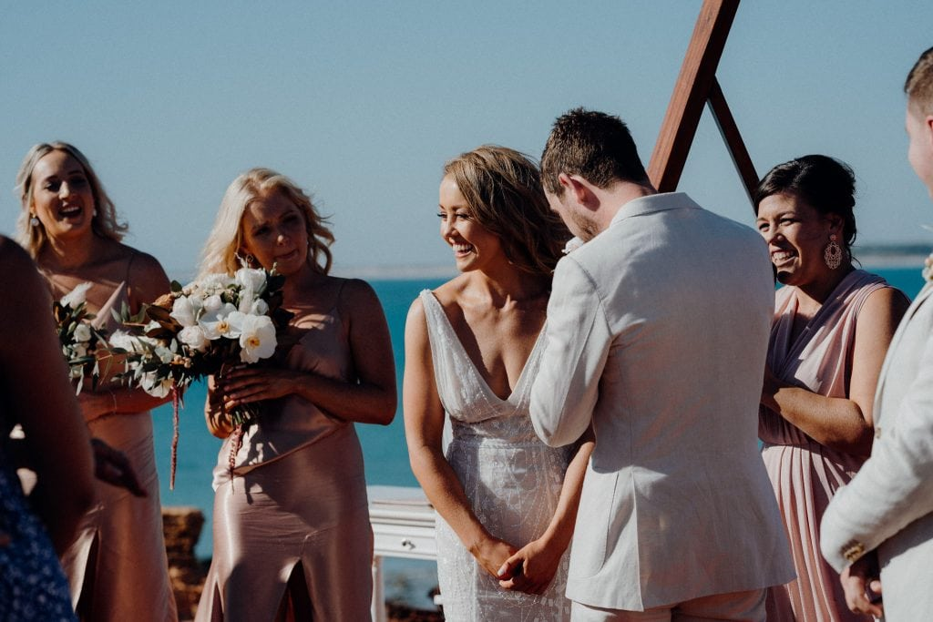 bride smiling at her guests during wedding ceremony in Broome with blue ocean as backdrop