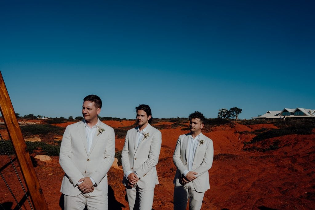 three groomsmen in white suits on red rocks at wedding at Gantheaume Point in Broome