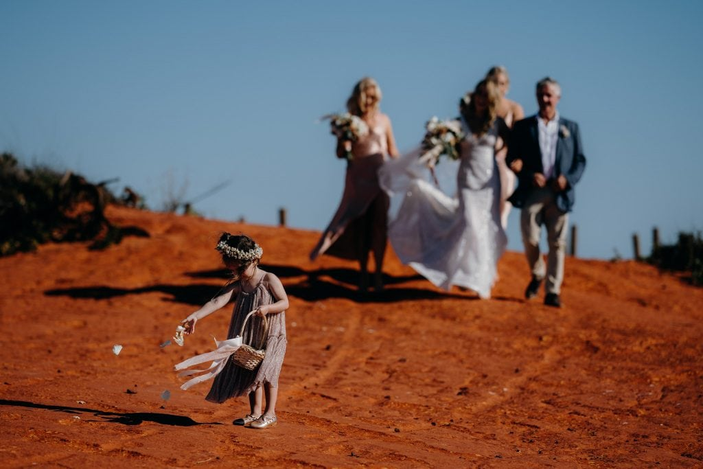 little girl with basket throwing flowers with bride and her parents following
