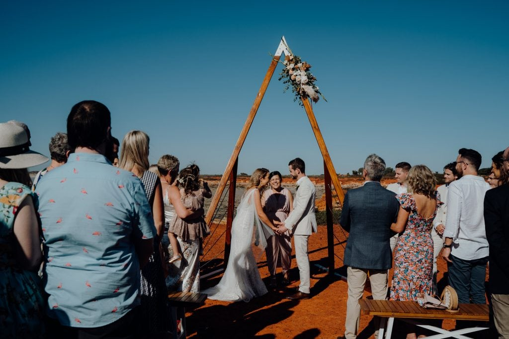 wedding ceremony taking place in the full sun with bride and groom standing in the center under a wooden arbour
