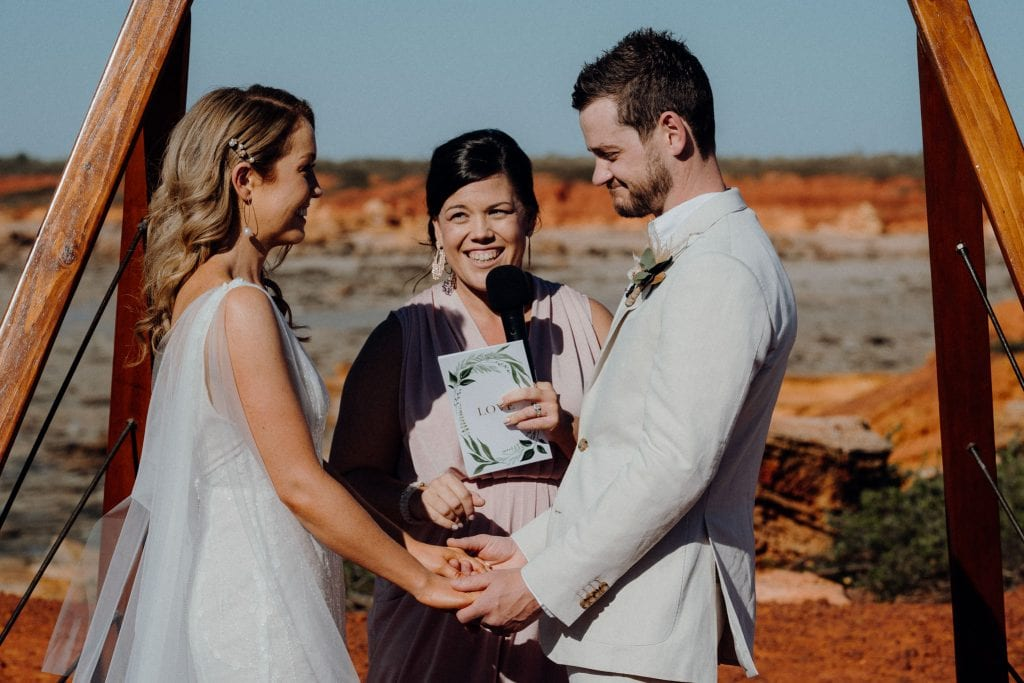young couple are holding hands during their Gantheaume Point wedding ceremony with marriage celebrant standing between them