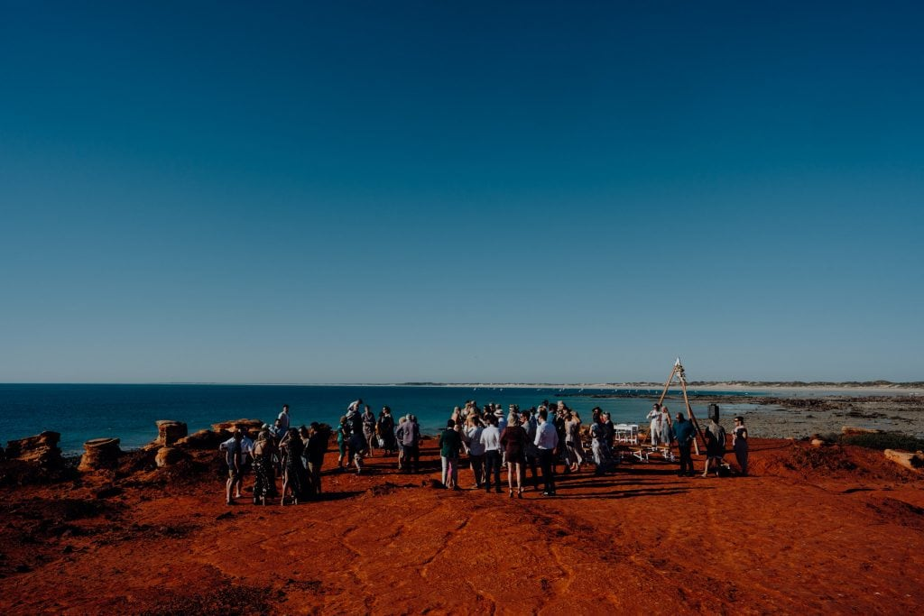 wedding guests mingling on clifftop with ocean views and Cable Beach in the distance