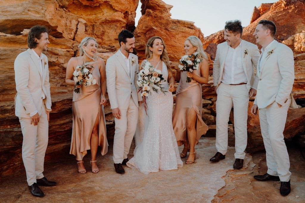laughing bride and groom with their bridal party surrounded by rocks