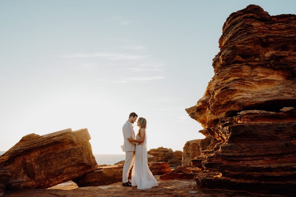portrait of young wedding couple dressed in white standing facing each other with sun setting behind them