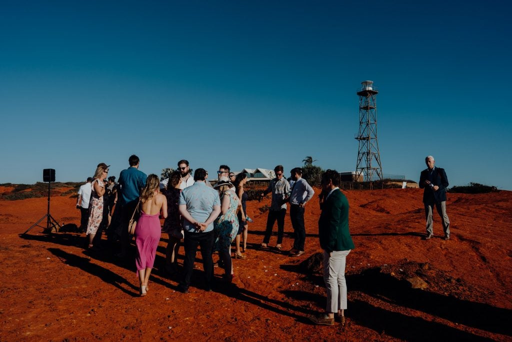 group of people mingling and chatting at wedding at Gantheaume Point near lighthouse