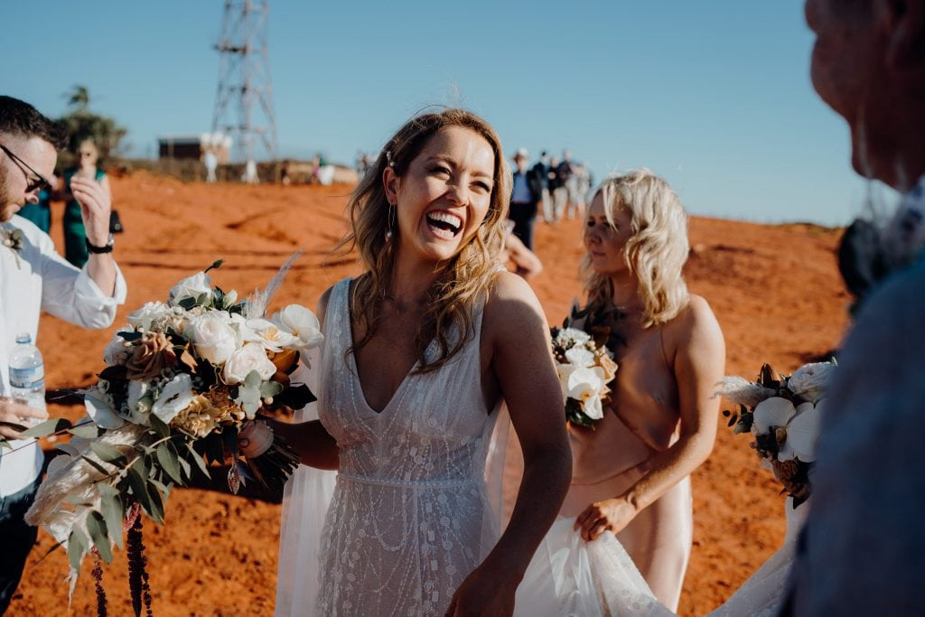 laughing bride in white dress and flower bouquet in her hand