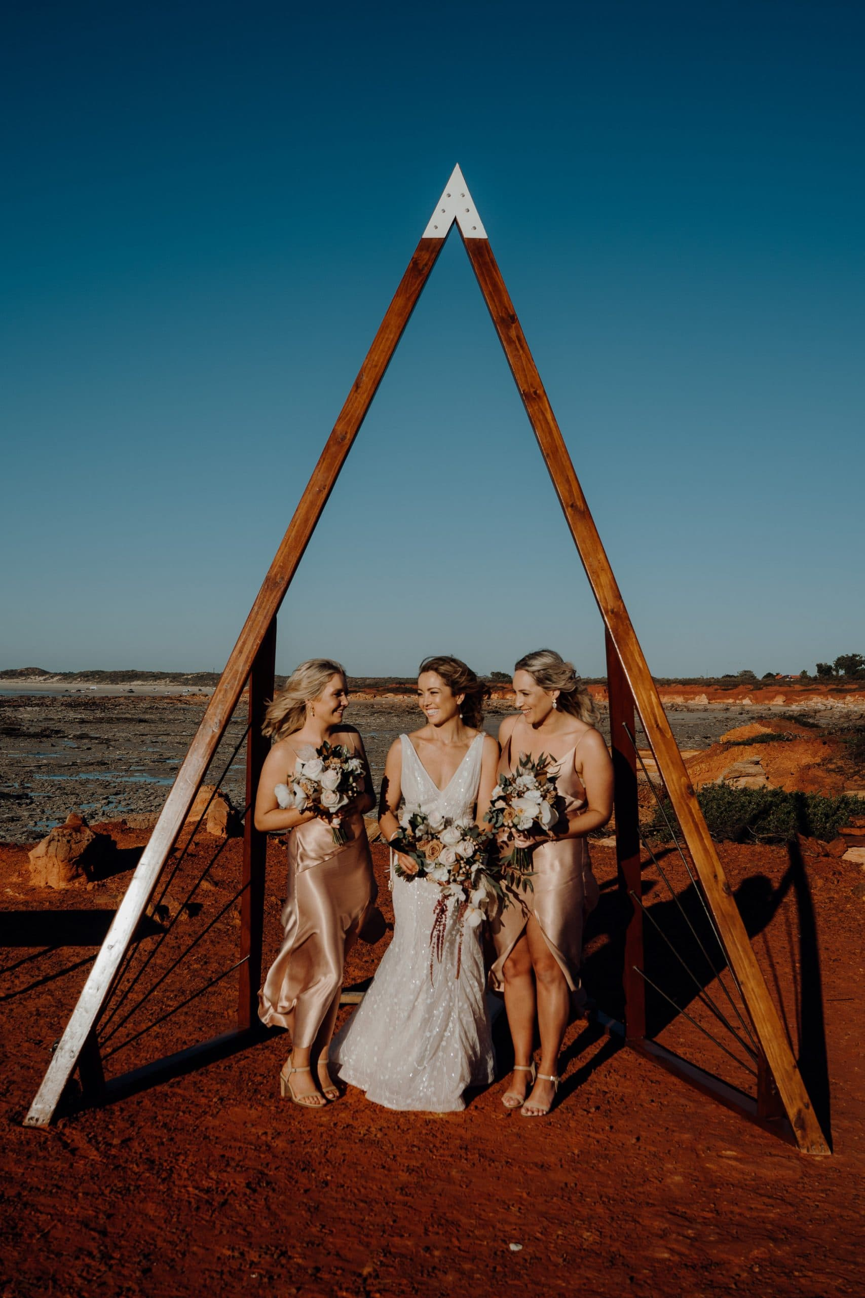 young beautiful bride and her two bridesmaids under a triangular wooden arbour with flower bouquets