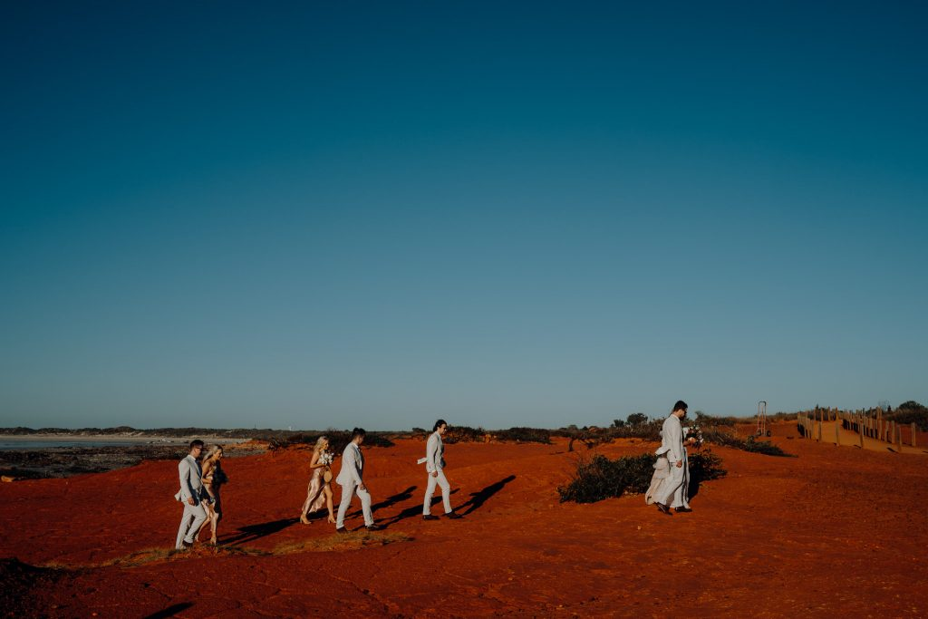 bridal party walking around the red rocks at Gantheaume Point in Broome