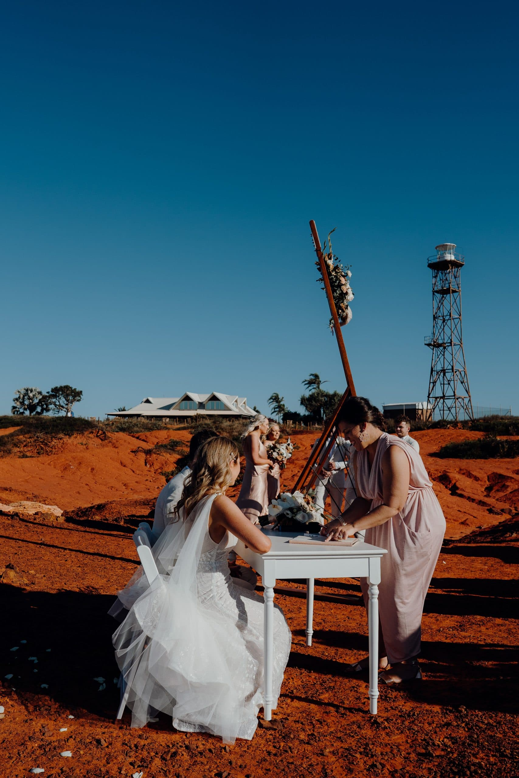 signing of wedding documents with Elle Saunders celebrant and Gantheaume Point lighthouse in the background