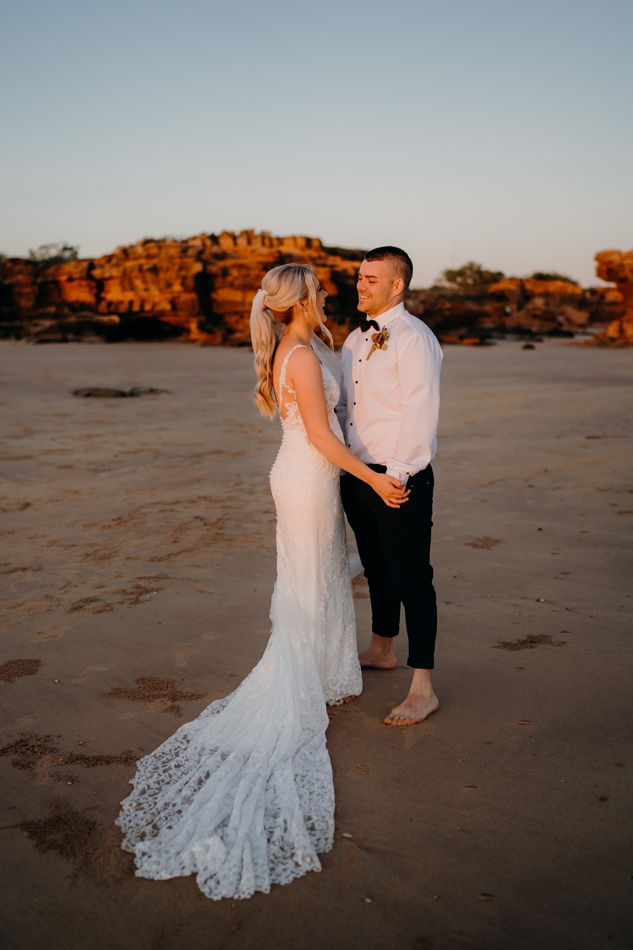 wedding couple holding hands looking at each other with red cliffs behind them